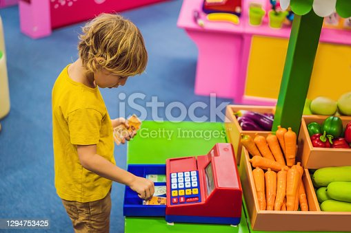The boy plays with the children's cash register. financial literacy for children.