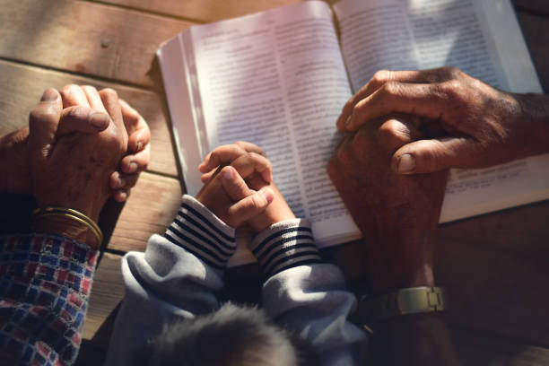The boy prayed on the table. The family prayed together. stock photo