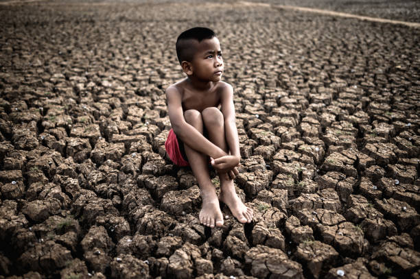 The boy sit hugging their knees bent and looking at the sky to ask for rain on dry soil. stock photo