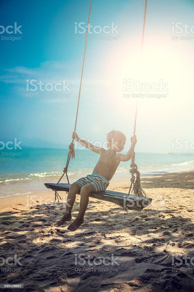 The boy sitting on swing on the beach stock photo