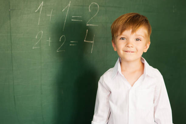The boy solved arithmetic equations at school. A child writes on the blackboard. Schoolboy about a board solves examples. Back to school concept. stock photo