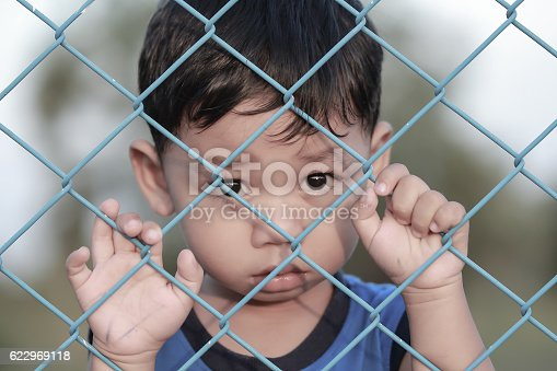 istock The boy standing of  pulling a metal fence . 622969118