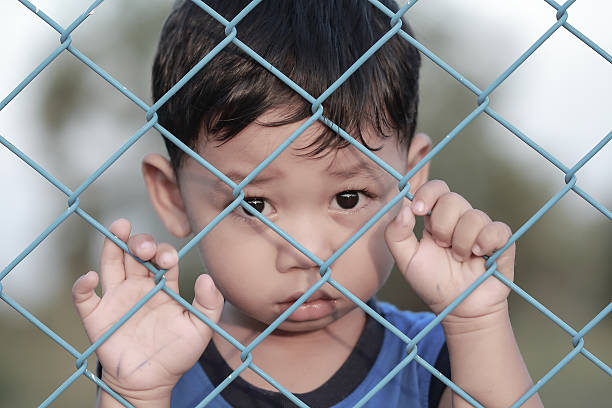 The boy standing of  pulling a metal fence . stock photo