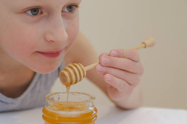 the boy using a spoon for honey eats it from the jar. - kiss стоковые фото и изображения