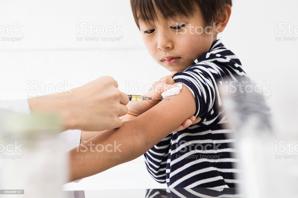 The boy who receives vaccination stock photo
