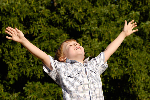 The boy with open hands lifted to sky stock photo