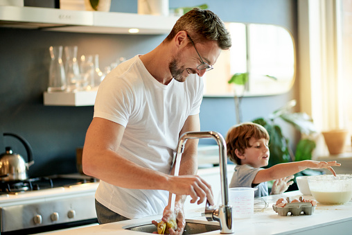 Shot of a father and his adorable son baking together at home