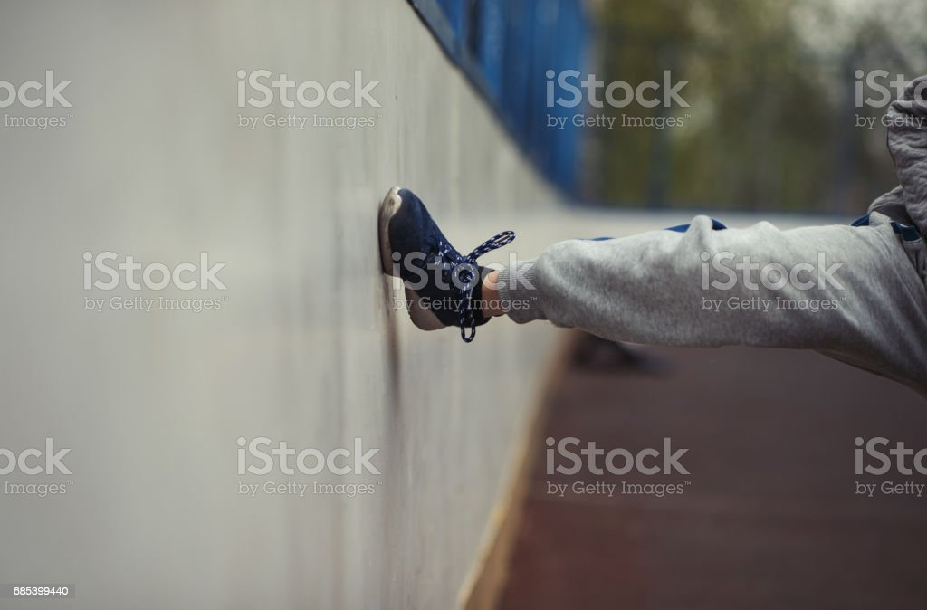 The boy's leg hits the wall of the basketball field. The boy lost the game stock photo