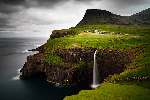 the breath taking view of gasadalur with a waterfalls - faeröer stockfoto's en -beelden