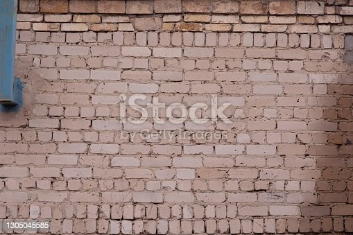 The brick wall of the building is made of white brick. Rear view. Blue chimney stack.
