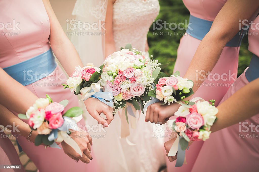 The bride and bridesmaids are showing beautiful flowers on their stock photo