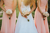 istock The bride and bridesmaids in an elegant dress is standing and holding hand bouquets of pastel pink flowers and greens with ribbon at nature. Young beautiful girls holds a wedding bouquet outdoors. 1137291609