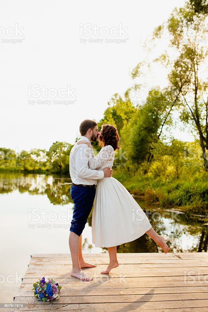 The bride and groom are standing on a wooden pier stock photo