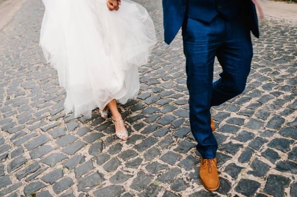 The bride and groom holding on hands and walking on road in the nature. Outdoors. Down view at shoes.