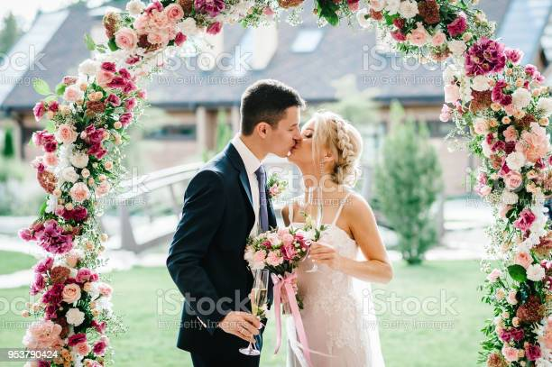 The bride and groom kissing newlyweds with a wedding bouquet holding picture id953790424?b=1&k=6&m=953790424&s=612x612&h=3xusxojdhm5dvv0mn1 3k6lrlkeljtf mw u9otfj38=
