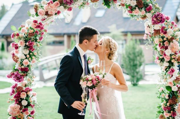 a noiva eo noivo beijando. recém-casados com um buquê de casamento, segurar copos de champanhe em pé na cerimônia de casamento sob o arco decorado com flores e verdura de ao ar livre. - casamento - fotografias e filmes do acervo