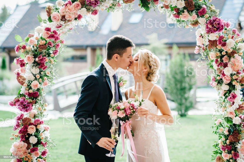 La novia y el novio besándose. Recién casados con un ramo de novia, sosteniendo vasos de champán de pie en la ceremonia de la boda bajo el arco adornado con flores y vegetación de al aire libre. - foto de stock