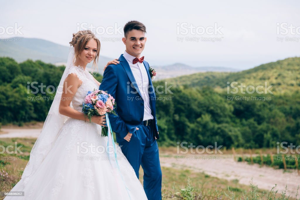 The bride and groom stand in the field against the backdrop of vineyards and fields. The girl is holding a bouquet of flowers and slightly squinting from the sun. The guy smiles and holds his hands in his pockets. The couple are happy to be in this place royalty-free stock photo