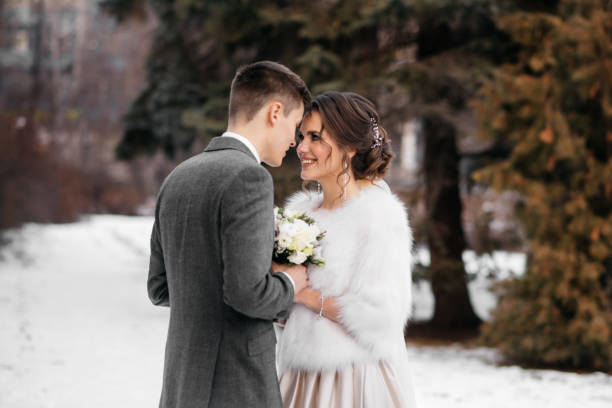 The bride and groom stand in the winter park, huddled together stock photo