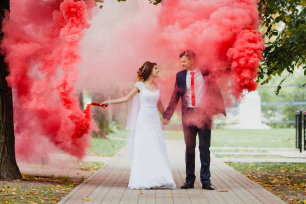 The bride and groom with the red colored smoke stock photo