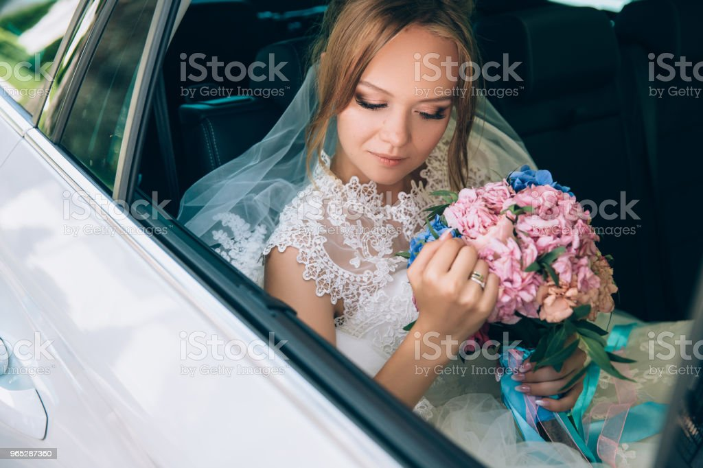 The bride carefully arranges the flowers in the bouquet while sitting in the car. The girl looks at the wedding bouquet and thinks about her beloved zbiór zdjęć royalty-free