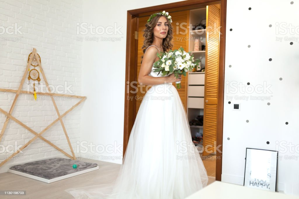 The Bride In A Beautiful Wedding Dress With A Long Curly Hair