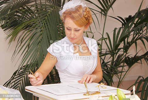 The bride in a wedding dress signs the marriage documents.