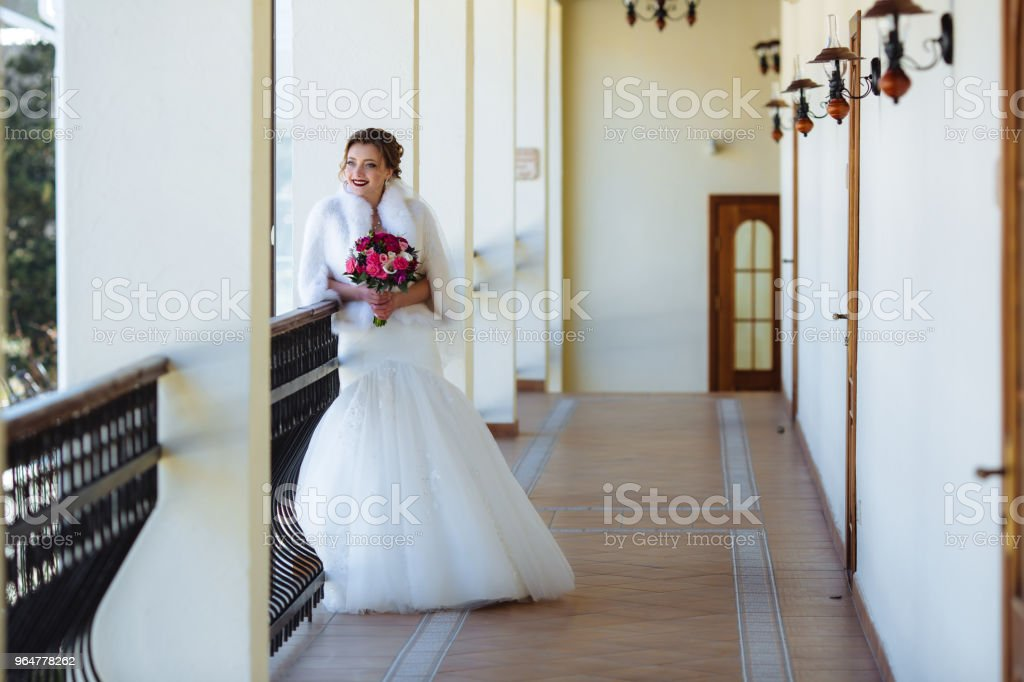 The bride in a white dress with a tight skirt is standing on the balcony and admiring the nature. The girl is holding a bouquet of pink flowers royalty-free stock photo