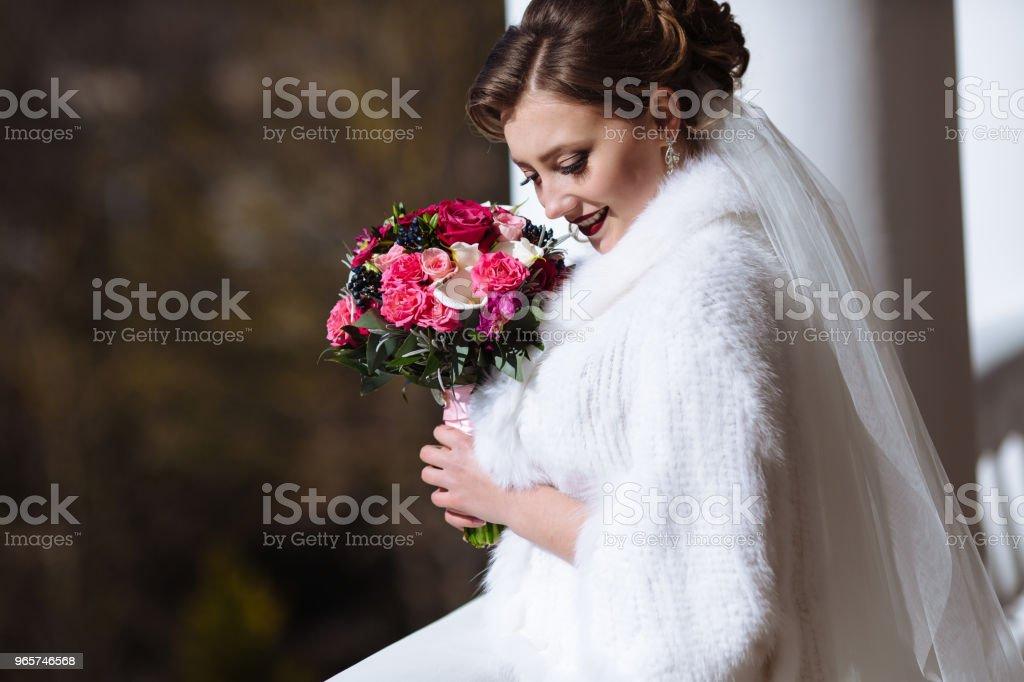 De bruid in witte kleren lacht en heeft leuke op straat. Portret van een jong meisje met een boeket, verlaagde ze haar ogen en toont haar mooie make-up - Royalty-free Avondjurk Stockfoto