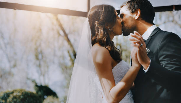 The bride is his to kiss Cropped shot of an affectionate young newlywed couple kissing on their wedding day wedding stock pictures, royalty-free photos & images