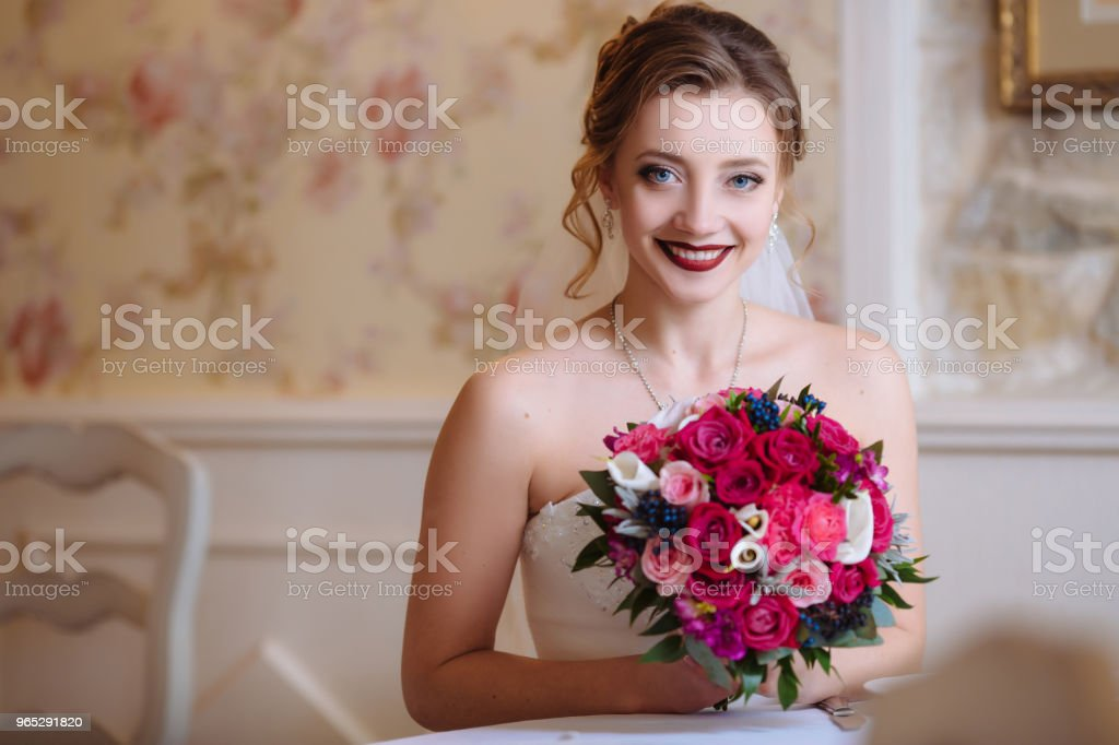 The bride is holding a bouquet of red flowers and smiling happily sitting at the table. A girl with blue eyes and curls gets married zbiór zdjęć royalty-free