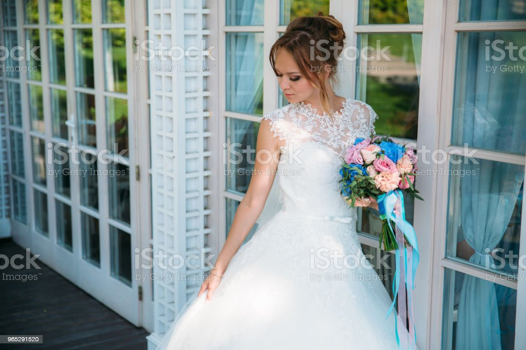 The bride is looking at her beautiful white dress on the background of the glass doors of the big hall royalty-free stock photo