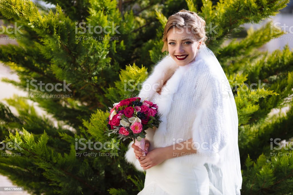 The bride is smiling broadly and standing against the background of greenery in the garden, holding a bouquet of roses, lips are painted with bright lipstick royalty-free stock photo