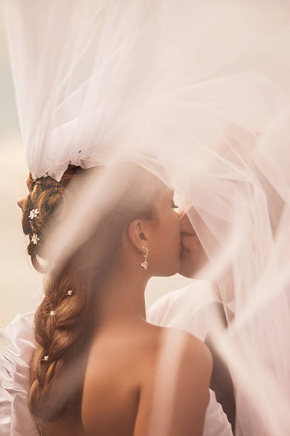 the bride kisses the groom under the veil - flitterwochen kleid stock-fotos und bilder