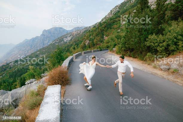 Photo of The bride rolls on a skateboard and holds the hand of the groom, who runs alongside along the highway in the mountains