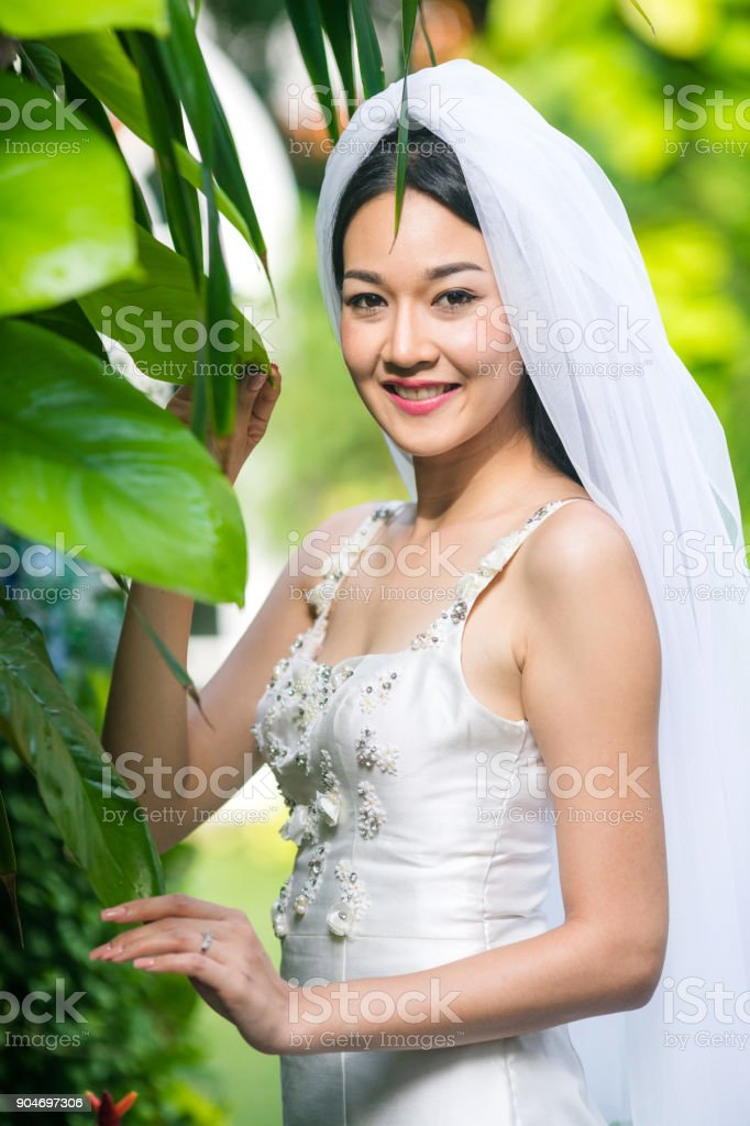 The bride take photo with a ring in the garden. stock photo