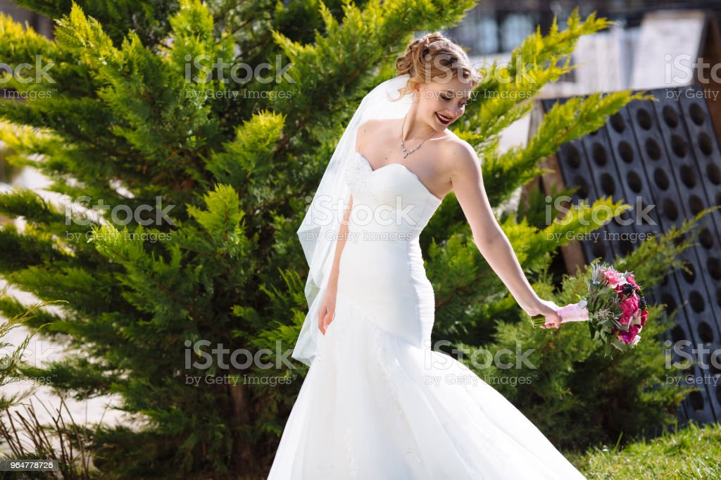 The bride walks in the park among the firs, has fun and plays with her wedding bouquet. Slender smiling girl in a white dress royalty-free stock photo