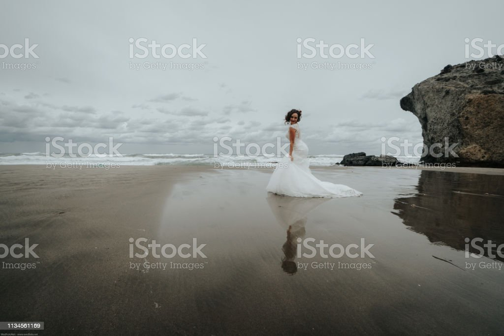The bride walks on the beach reflected in the sea water. Panoramic...