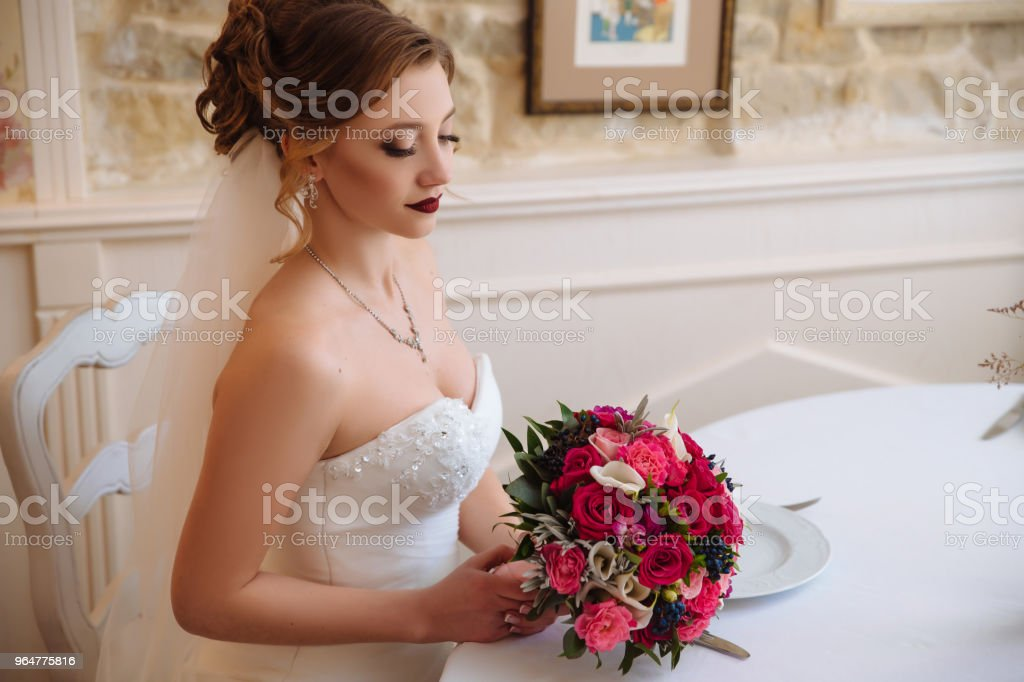 The bride with curls and red lips sits in a bright hall and admires her bright bouquet of red and pink roses royalty-free stock photo