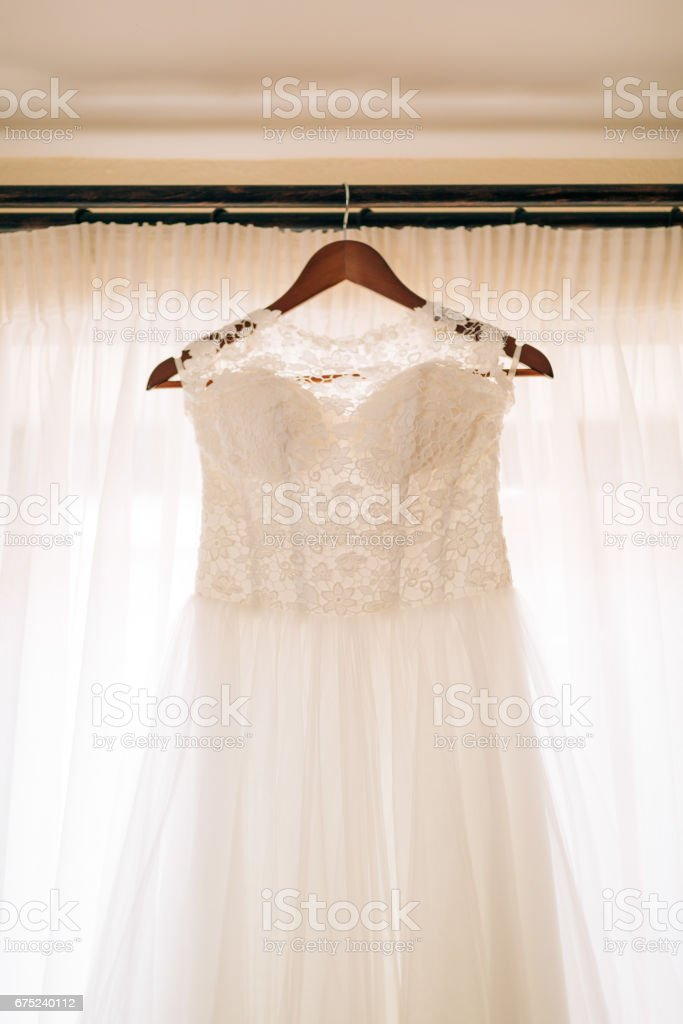 The bride's dress hangs on the cornice royalty-free stock photo
