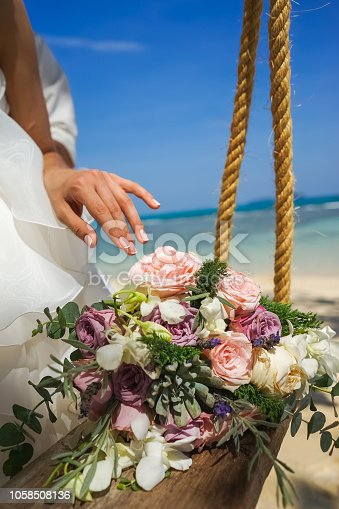The brides hand elegantly touches a wedding bouquet of roses on a swing against the background of the sea Tropical landscape, the sea of sand and sky.