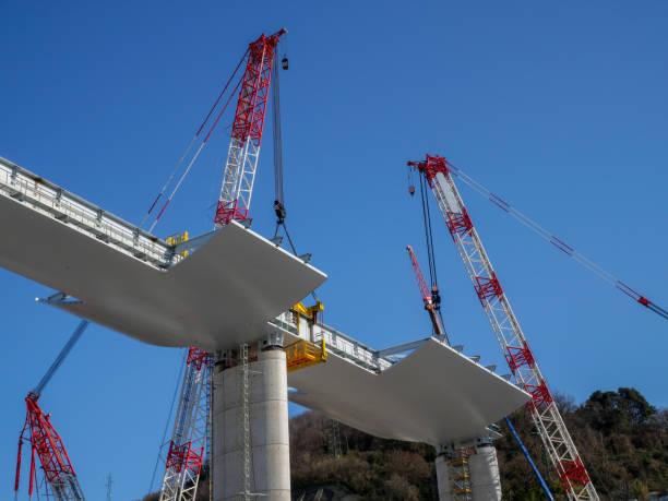 les grues de pont soutiennent la travée - pont gênes photos et images de collection