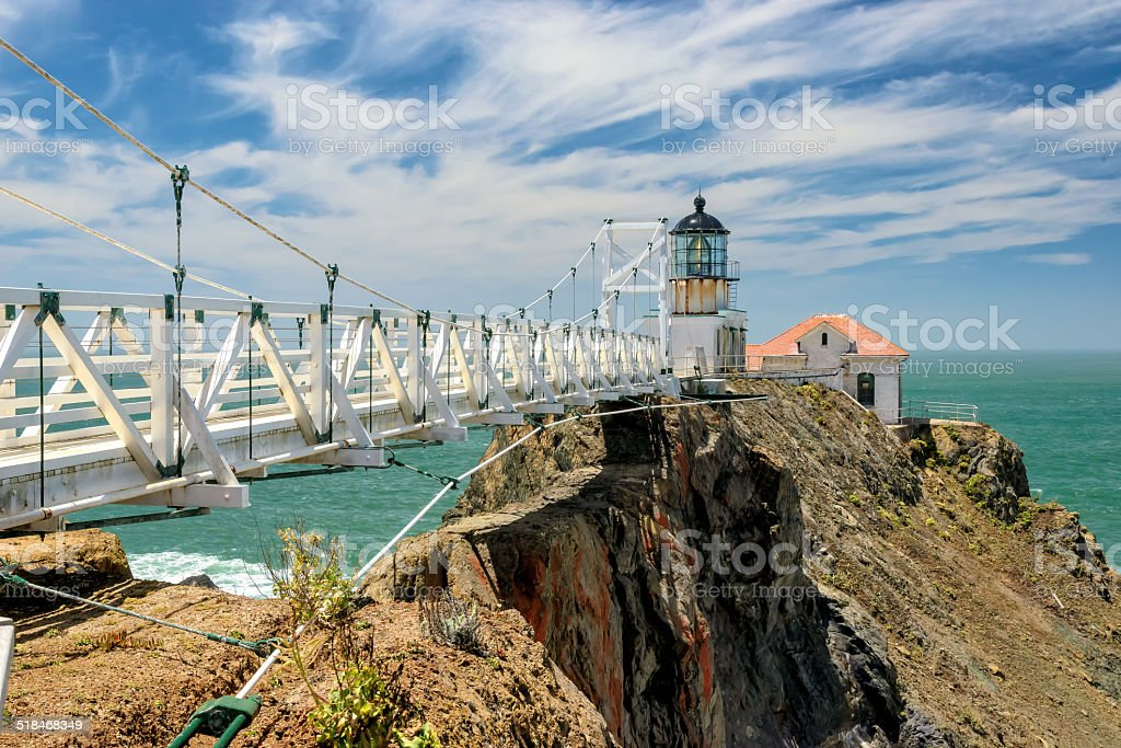The bridge to lighthouse on the rock in the sea. stock photo