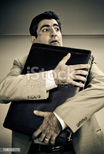a hispanic businessman hugging his briefcase while looks around nervously
