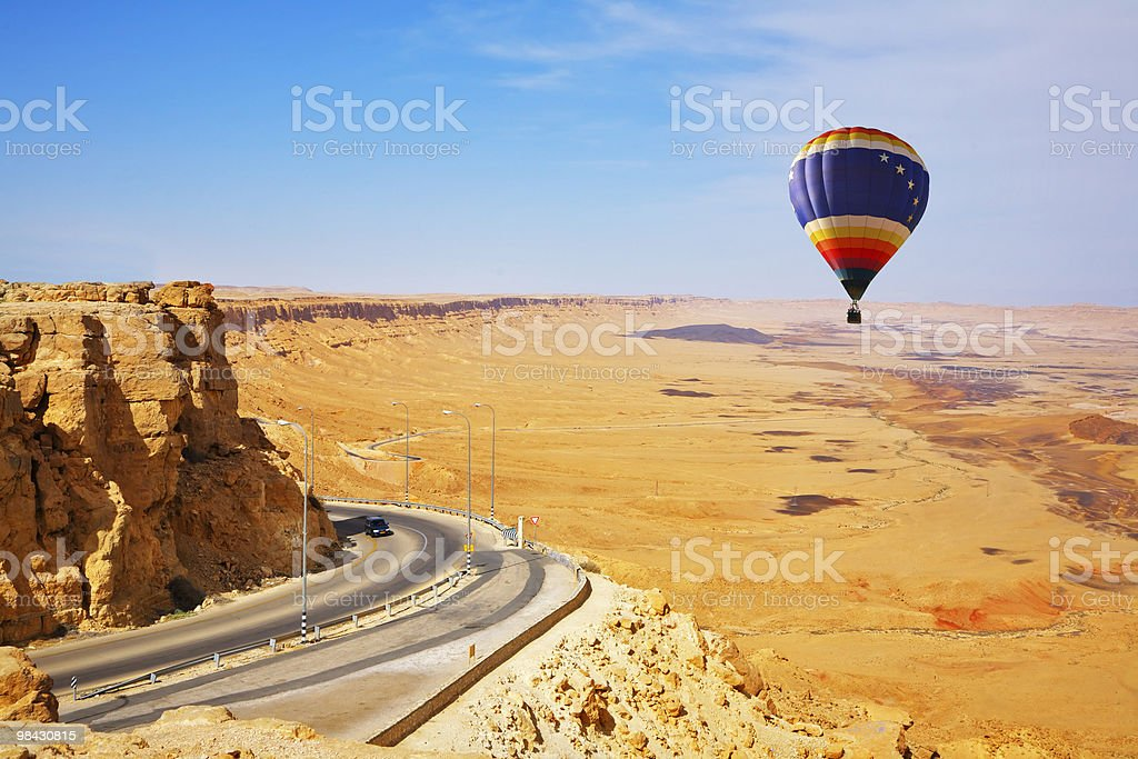 The bright decorative balloon soars above road to desert royalty-free stock photo