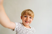 Photo of a smiling blonde boy; studio shot, isolated on a white background.