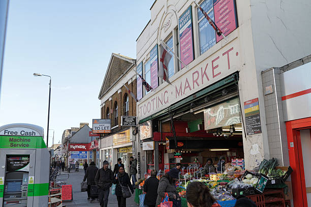 Tooting Broadway Market London SW17 exterior The Broadway Market, across the road from Tooting Broadway Underground Station in London SW17, houses over 100 traders in a large building. Between them, the traders represent many nationalities and sell many different goods, from fruit and saris to luggage. whiteway stock pictures, royalty-free photos & images