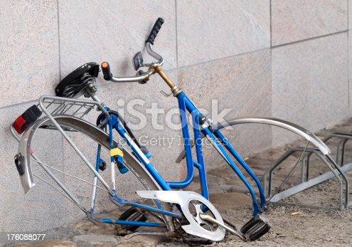 Discarded woman's bicycle leaning against a concrete wall.