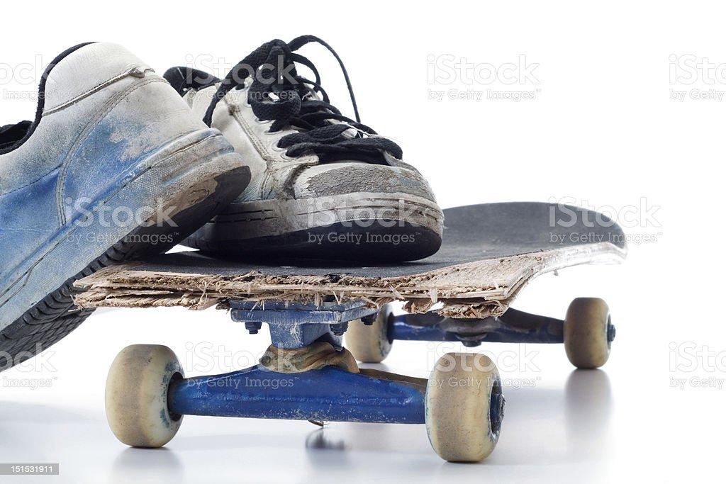 The broken skateboard and worn sports footwear stock photo