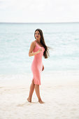 The brunette in a pink fitting dress walks on a snow-white beach.